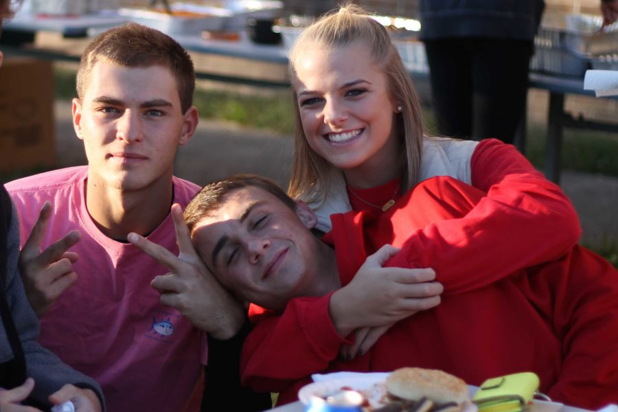 Juniors Cole Hilt, Madison Calhoon, and Bailey Sanders hang out at the senior tailgate before the game.