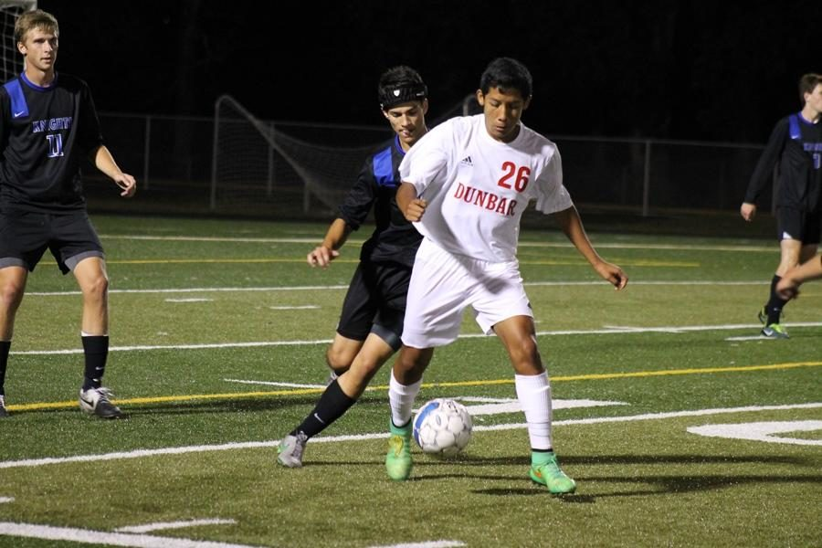 Number 26, Eddie Andrade, keeps the ball from opposing player.
