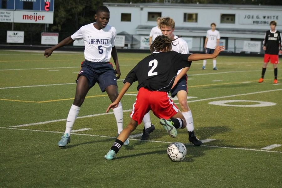 Number 2, Amir Simons, plays the ball past opposing players.