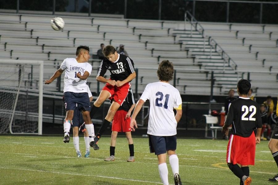 Number 13, Justin Kelley, goes up for a header with opposing player.
