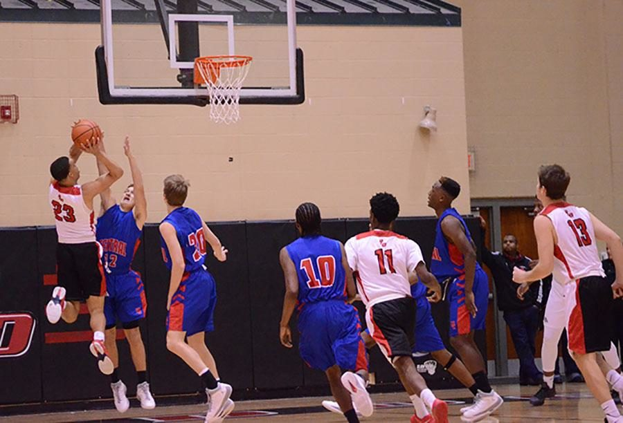 Number 23, Darius Williams, shoots over opposing player.