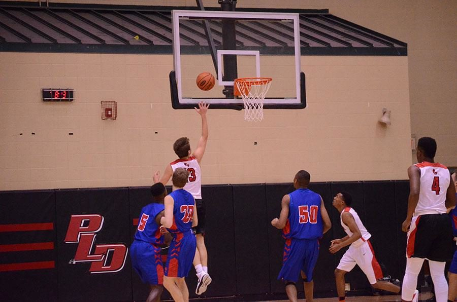 Number 13, Justin Kelley, goes in for a lay-up.