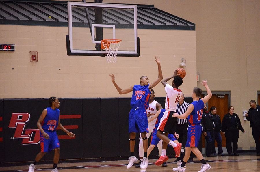Number 11, Taveion Hollingsworth, goes in for a shot over an opposing player.
