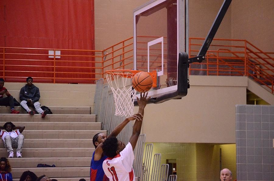 Taveion Hollingsworth shoots a lay-up despite the opposing player against him.