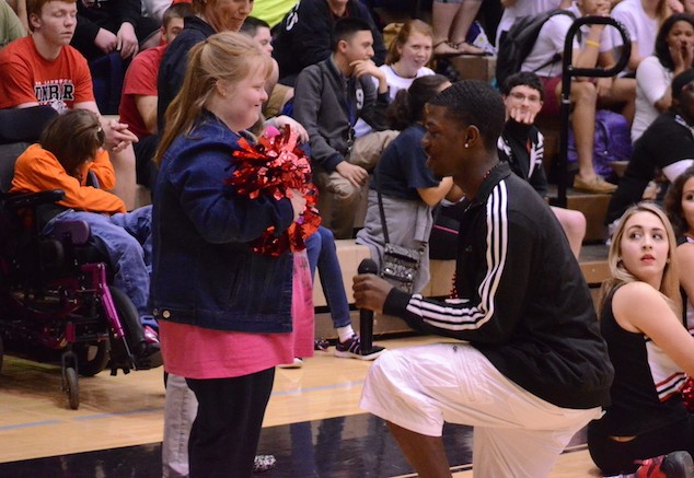 Mallory Burrows shows a heartfelt smile while Halkeiem Lewis is down on one knee during the pep rally promposal.