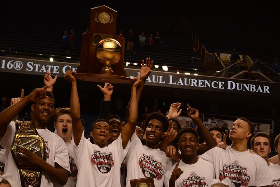 Senior Jordan Lewis holds the championship trophy while his teammates celebrate the win