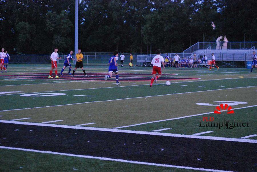 #25 Jack Sheroan dribbles down the field.