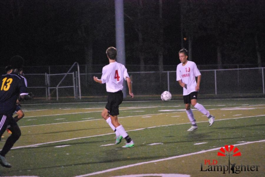 #13 Pedro Jaminiz prepares to deliver a pass to #4 Michael Vanderburg