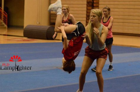 Senior Abby Rawls spots middle-schooler Hayden Woods on her back tuck