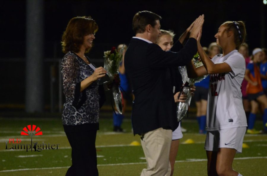 Senior Jessie Rajcan high fives her father.