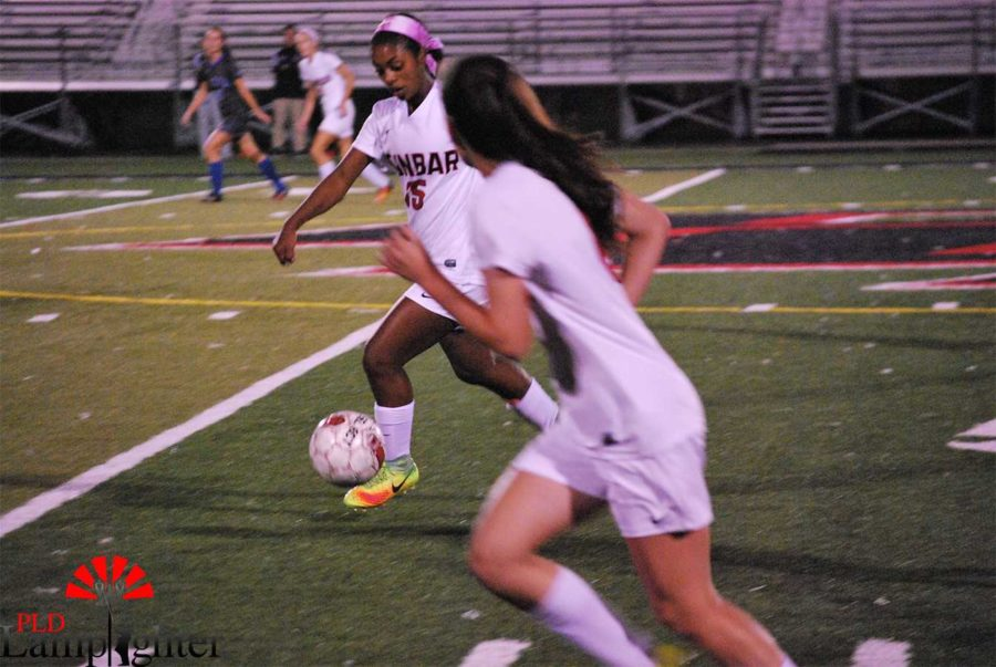 #15 Meron Roach dribbles the ball down the field.