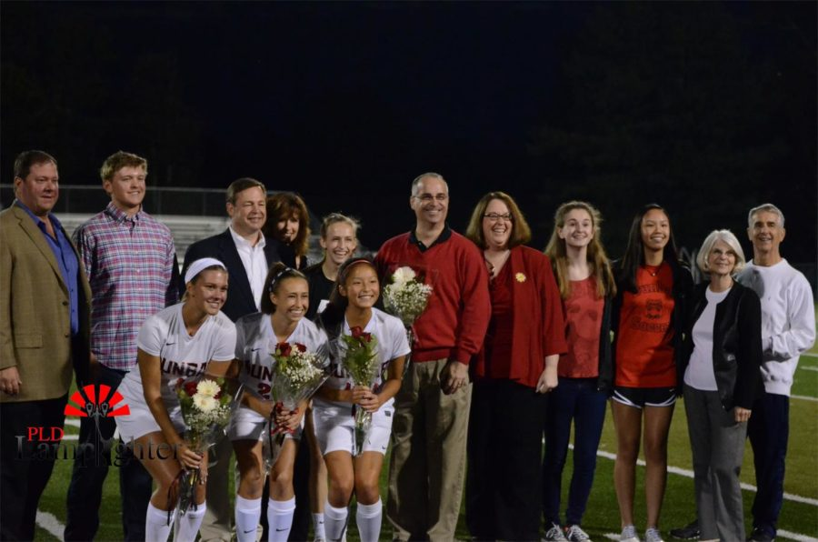 The three seniors pose for a photo with their families.