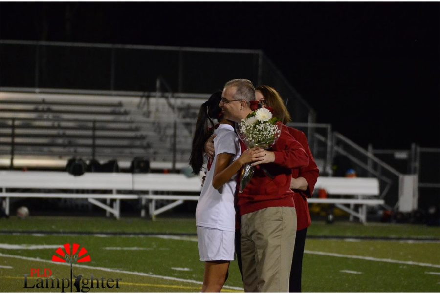 Senior Grace Kelly hugs her father.