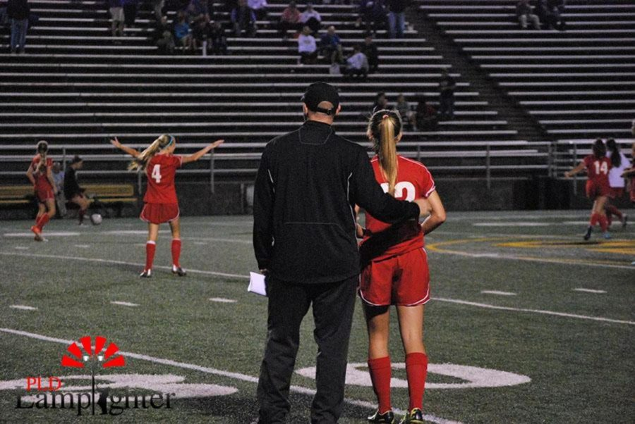 Coach Tom Morgan hugs Junior Baylee Lanter before warm-ups.