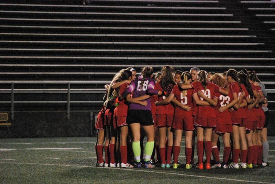 Dunbar soccer team huddle together.