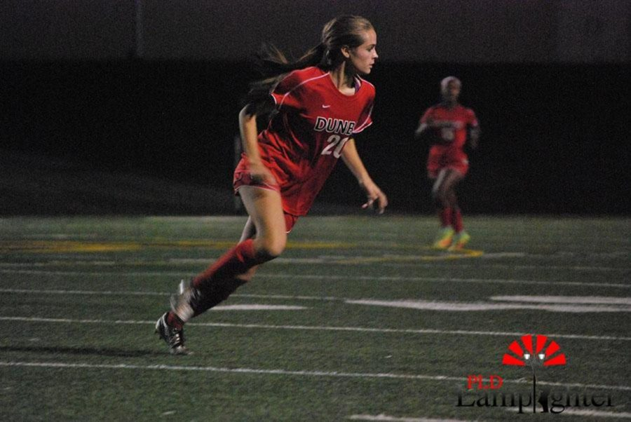 Junior Sophia Mitchel races to the ball.