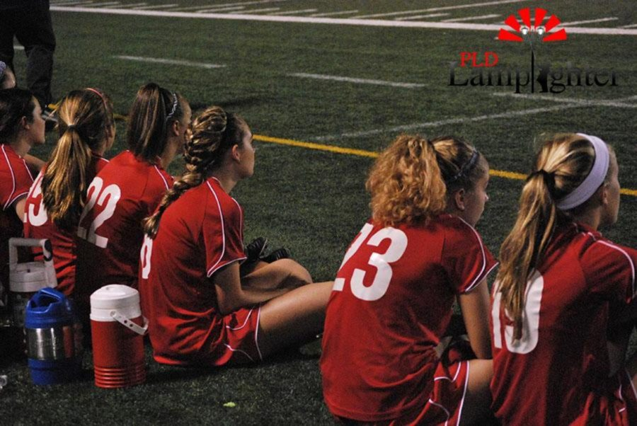 Dunbar Soccer girls watch their teammates from the sidelines.