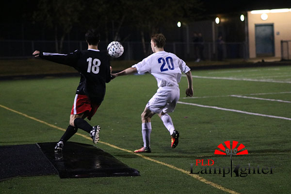 #18 Jackson Akins gets the ball from his opponent.