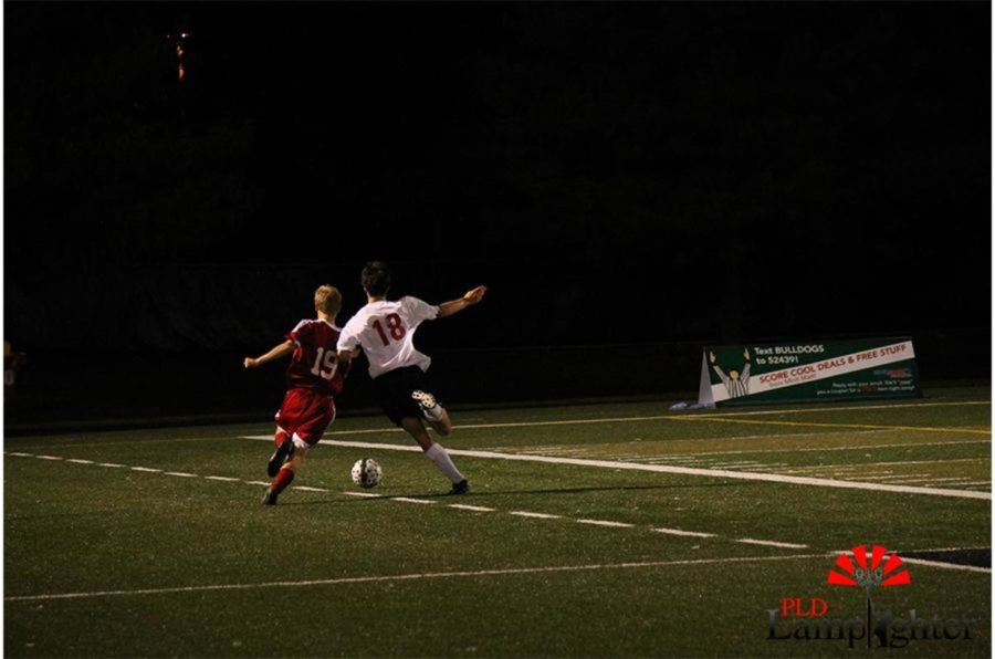 #18 Jackson Akins kicks the ball away from his opponent.