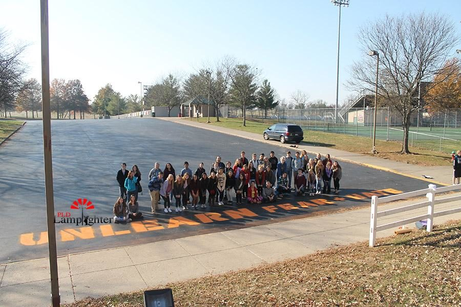 Students pose by the 60-ft Unlearn Fear + Hate mural.