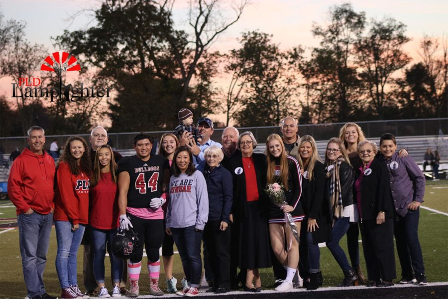 The families of Carter Hayslett (#44) and Maddie Carter pose together for a photo.