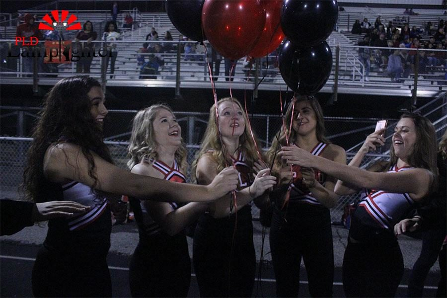 Senior dance team members release balloons at their last football game.