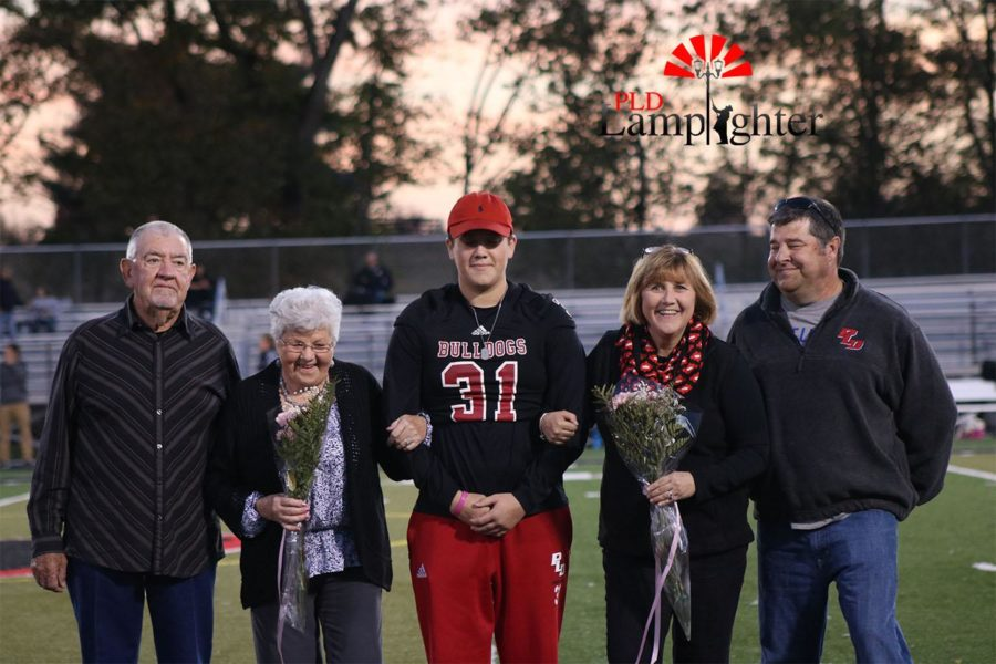 The family of Carter Delk (#31) escorts him on the field.