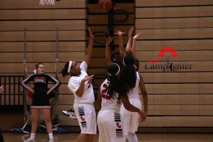 The girls reach up to catch a rebounding ball. They worked hard to gain more rebounds in an effort to get ahead in the game.