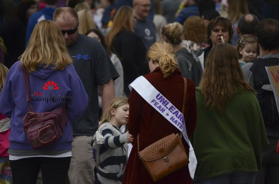 Many participants wore suffragette style sashes with the Unlearn Fear and Hate logo.