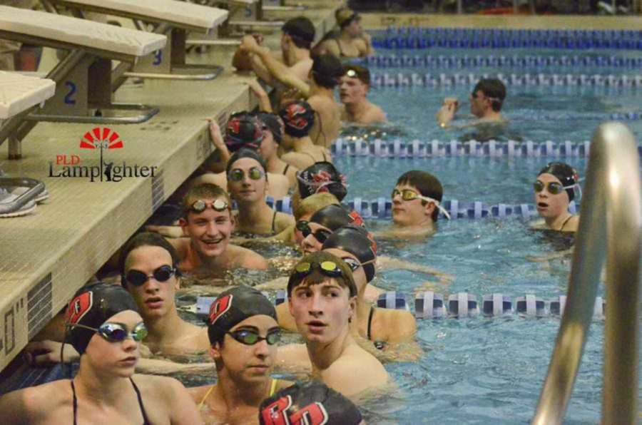 The PLD swim team listens to Coach Morgan Neuer during warm up time.