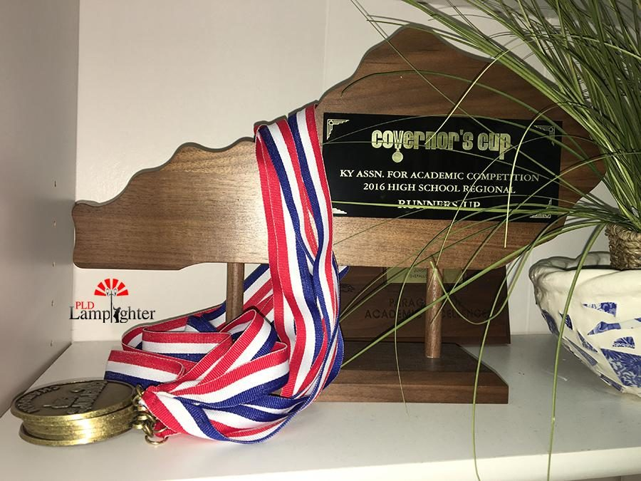 A Governor's Cup runner up trophy is displayed along with medals in Mrs. Susan Magadenz's classroom.