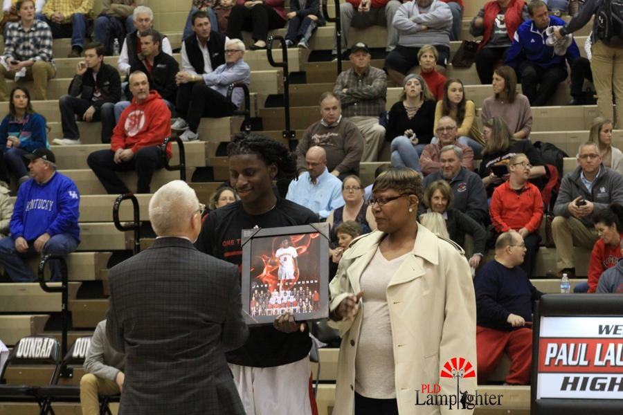 #0 Javea Richardson shaking Coach Chalks hand with his mom by his side.