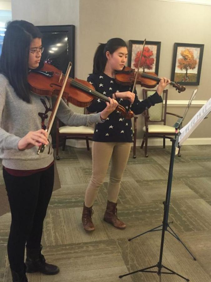 Sophomores Megan Guan and Stephanie Yang perform a violin-viola duet for the senior citizens.