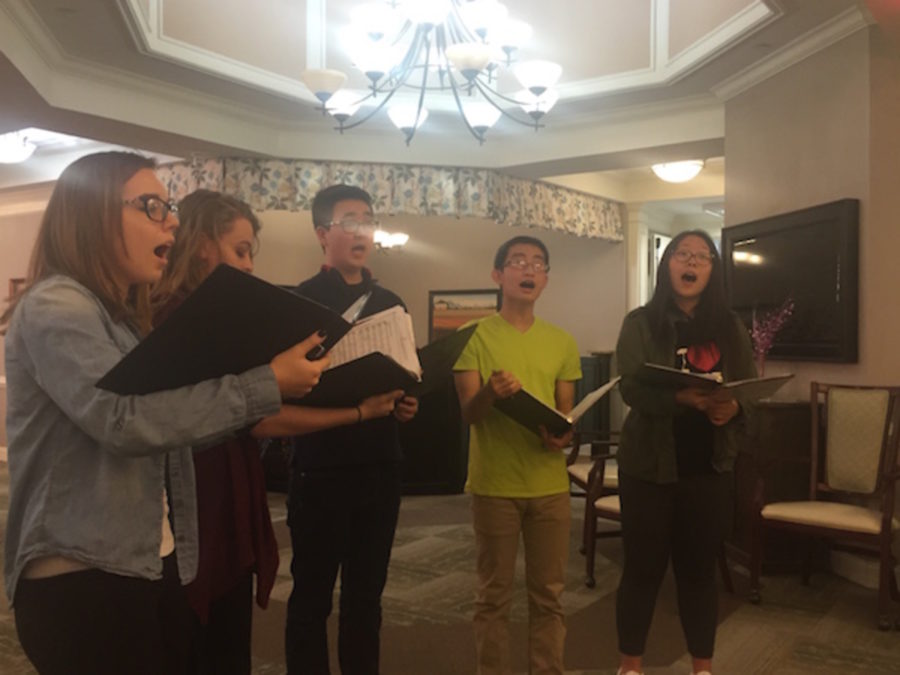 A group of members perform a choir piece for the senior citizens.