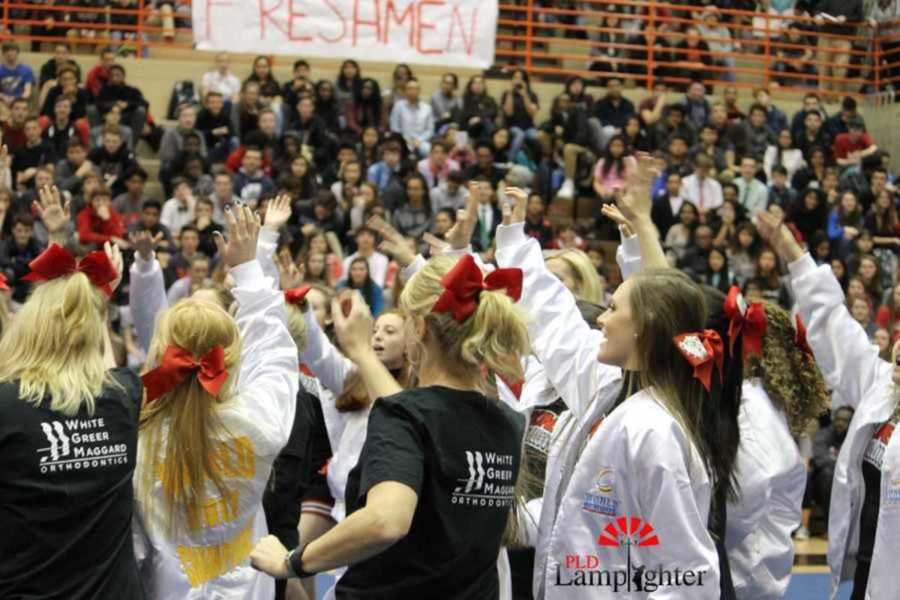 Teachers along with Dunbar Cheerleaders put their hands in for a cheer before the teachers' routine.