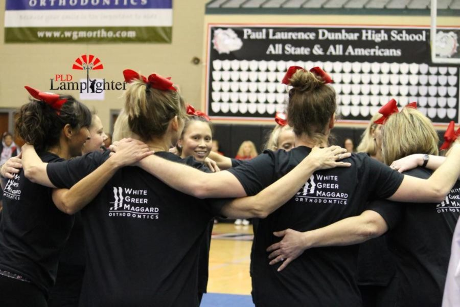 The teachers huddle up together before their cheer routine- like performance.
