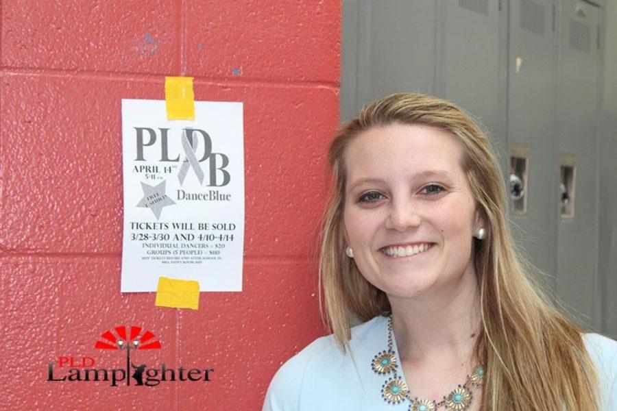 Student Council Officer Rachel Fister posing with a Dunbar Dance Blue flyer.