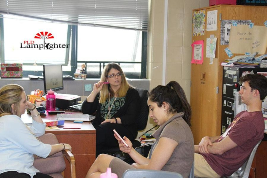 Student Council sponsor Mrs. Fain meets with officers Rachel Fister, Sahar Mohammazadeh, and Josh Syzdlik (left to right).