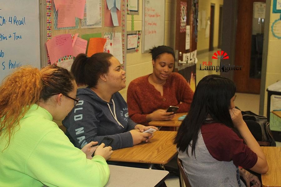 Students sit in Mrs. Burns' room and watch people sing in Karaoke Club.