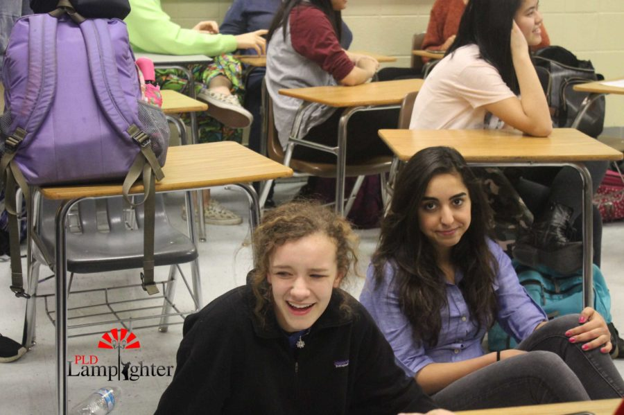 Juniors Molly Mohr and Sahar Mohammadzadeh sit and listen to people singing at Karaoke Club.