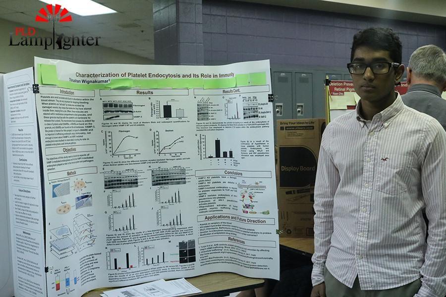 Senior Thirushan Wignakumar poses with his science fair poster.