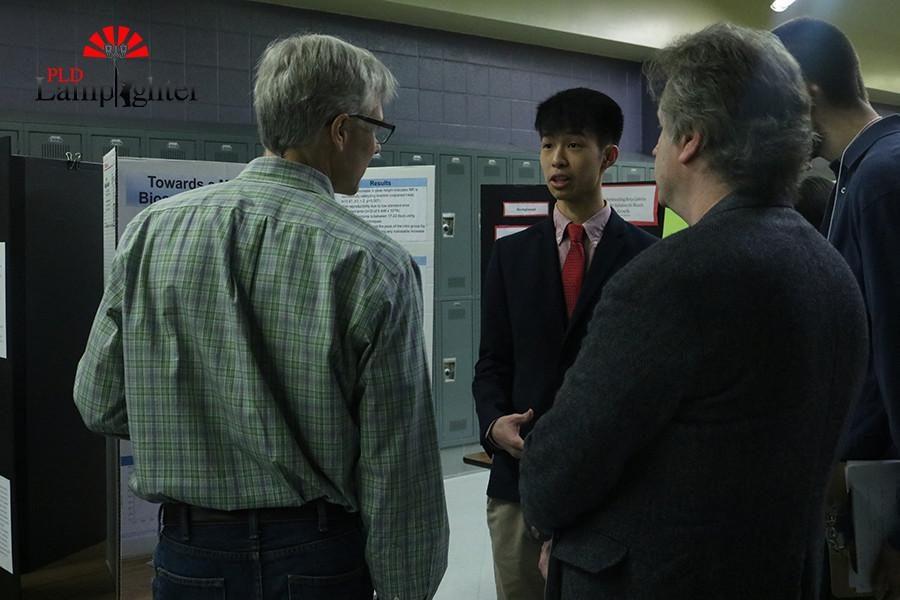 Senior Benjamin Xie presents his project to Science Fair judges.