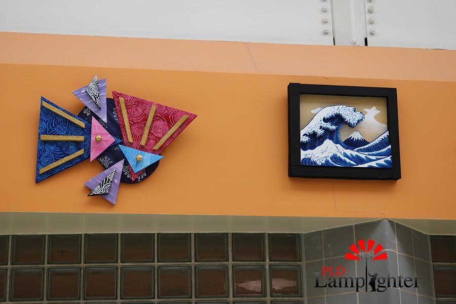 Student artwork hangs above the glass hallway.