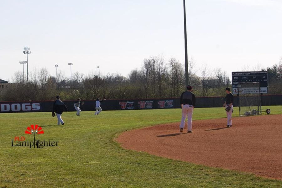 As the baseball season has officially started, players stand in the outfield practicing their delivery of pitches and throws while other members look on.
