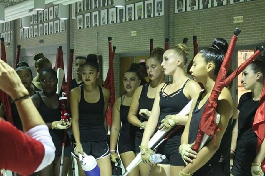 The members receive instruction from their coach before a performance.