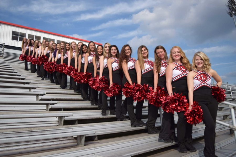 The dance team lined up in uniform on the bleachers.