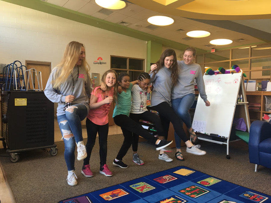 Juniors Virginia Smith, Rachel Wagers, and Elizabeth Lippert dance with the girls at Arlington Elementary.
