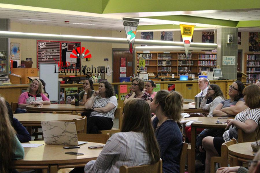Teachers watch the teacher appreciation video in the library.
