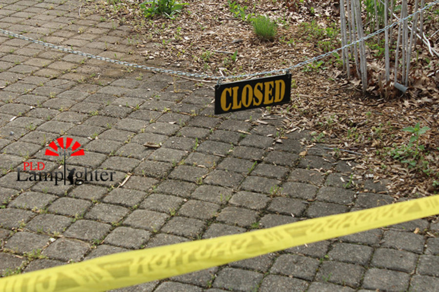 A sign stating that the memorial garden is closed hangs across the entrance, while the garden remains surrounded by caution tape due to the misuse by students.