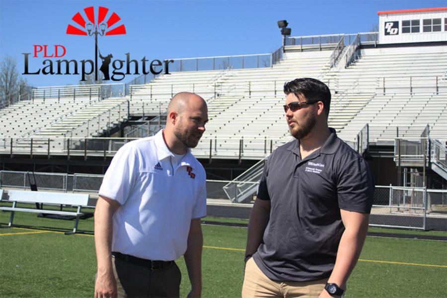 Athletic Trainer Cody Begley talking to Dunbar football coach Chris Mullens.
